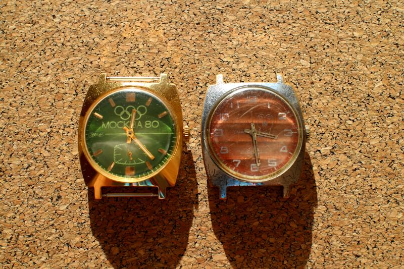 Часы ЗИМ с красным циферблатом и Олимпийским Мишкой 1980 год. Рядом часы ЗИМ с зеленым циферблатом и надписью Москва 80 в золотом корпусе